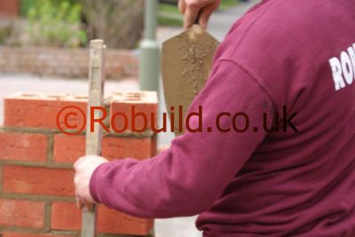 bricklayer using spirit level & brick trowel